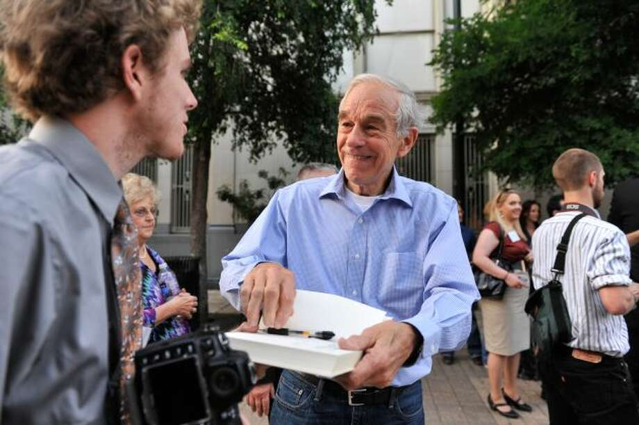 GOP presidential candidate Ron Paul signs a copy of his book after speaking to supporters at a rally in Main Plaza on Thursday, April 12, 2012. Photo: Robin Jerstad, For The Express-News