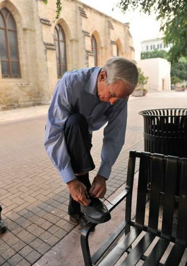 After leaving the Main Plaza stage, Ron Paul takes a quiet moment to work on his right shoe. Photo: Robin Jerstad, For The Express-News