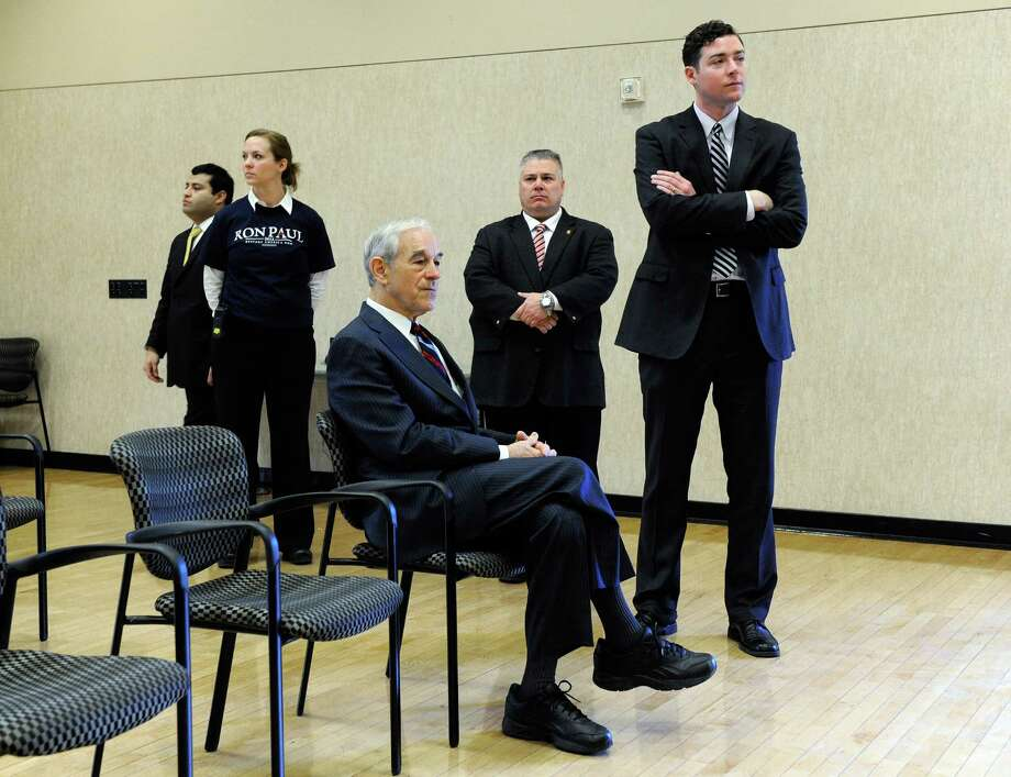 "Ron Paul sits while flanked by staff members as he waits to be introduced at a ""Hispanics in Politics"" event Feb. 1, 2012 in Las Vegas, Nevada. Photo: Ethan Miller, Getty Images / 2012 Getty Images"