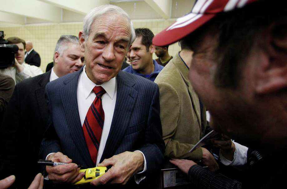 Republican presidential candidate Rep. Ron Paul, of Texas, left, signs a toy car during a campaign stop, Friday, Dec. 30, 2011, in Le Mars, Iowa. (AP Photo/Eric Gay) Photo: Eric Gay, Associated Press / AP