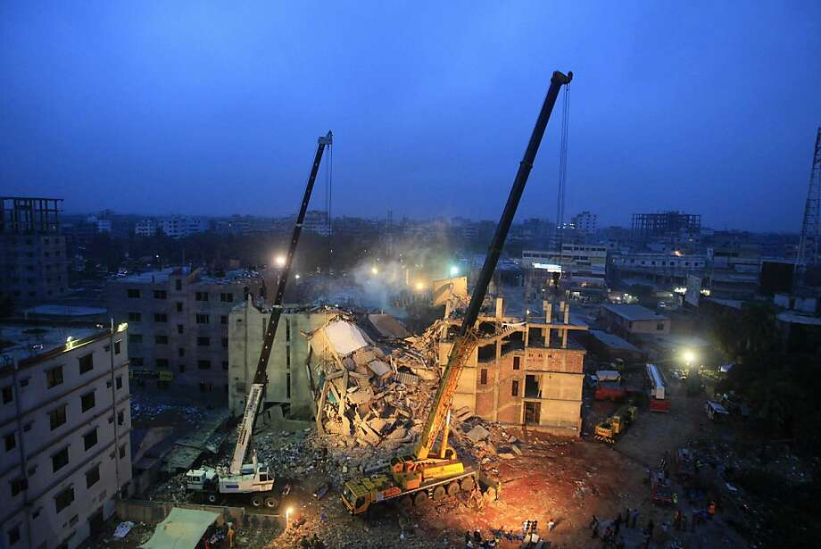 TOPSHOTS Cranes operated by Bangladeshi Army personnel are pictured at the scene following the April 24 collapse of an eight-storey building in Savar, on the outskirts of Dhaka, on April 29, 2013.  Bangladeshi textile bosses pleaded April 29 with Western clothing giants to keep doing business with them after nearly 400 people died in a factory collapse as hopes of finding more survivors faded. Organisers of the mammoth rescue effort ordered in cranes on Monday to clear the ruins of what was once an eight-storey factory compound before it caved in five days ago while some 3,000 textile workers were on shift. AFP PHOTO/STRSTRDEL/AFP/Getty Images Photo: Strdel, AFP/Getty Images