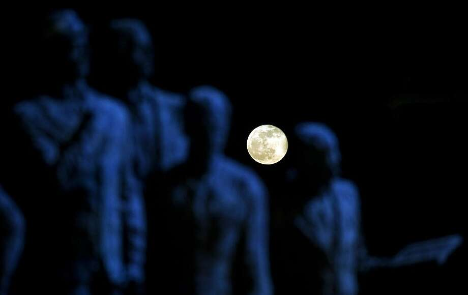 "A full moon rises behind the sculpture ""Gemidzi"" in Skopje, Macedonia. Photo: Robert Atanasovski, AFP/Getty Images"