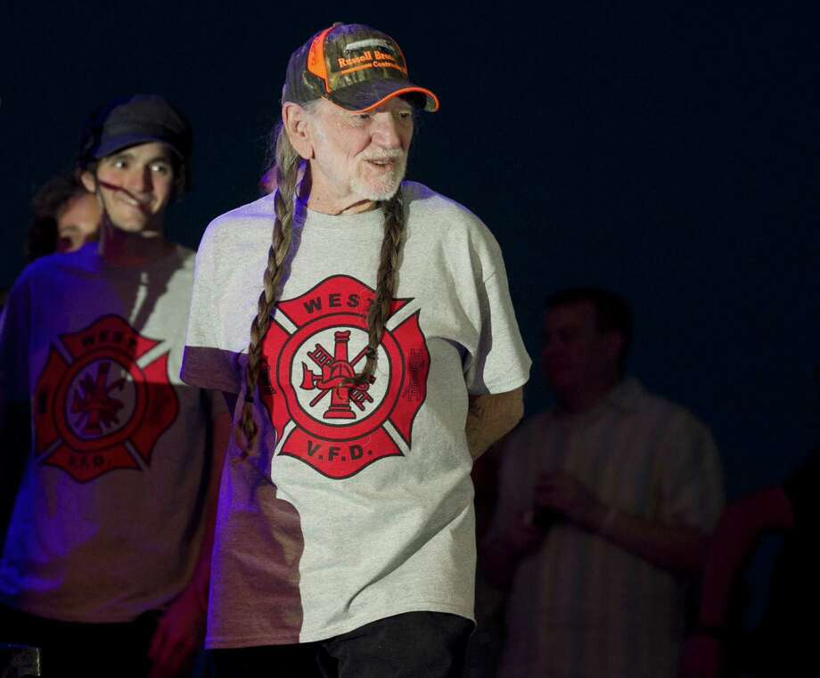 """Willie Nelson takes the stage wearing an """"I Support West VFD"""" T-shirt at his performance at The Backyard Live Oak Amphitheater in Austin, Texas, on Sunday, April 28, 2013. The concert was an early birthday celebration for Nelson, who turns 80 on Tuesday, and it was a benefit for the volunteer fire department in West, Texas, which is nearby where Nelson grew up in Abbott, Texas. A fertilizer plant exploded April 17 killing at least 14 people, including emergency responders, and hurting about 200 others. (AP Photo/Austin American-Statesman, Jay Janner) AUSTIN CHRONICLE OUT, COMMUNITY IMPACT OUT, MAGS OUT; NO SALES; INTERNET AND TV MUST CREDIT PHOTOGRAPHER AND STATESMAN.COM. Photo: Jay Janner, MBO / Austin American-Statesman"""