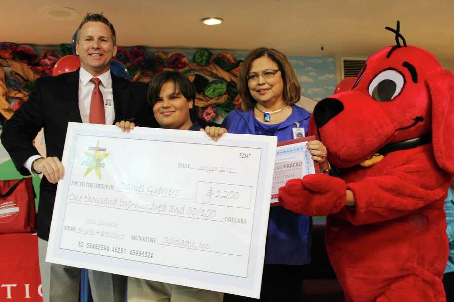 Beacon Hill Elementary School fourth-grader Daniel Guerrero receives a $1,200 prize check from Scholastic account executive Jack Darden (left), with SAISD administrator Vangie Aguilera and Clifford the Big Red Dog looking on.