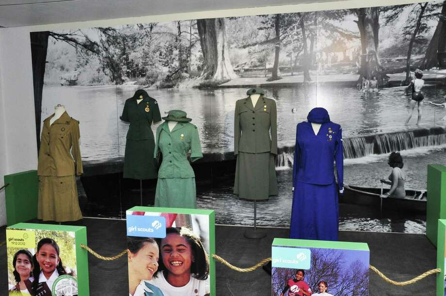 Classic Girl Scout uniforms are displayed in front of a background of Camp La Jita. Photo: Courtesy Girl Scouts