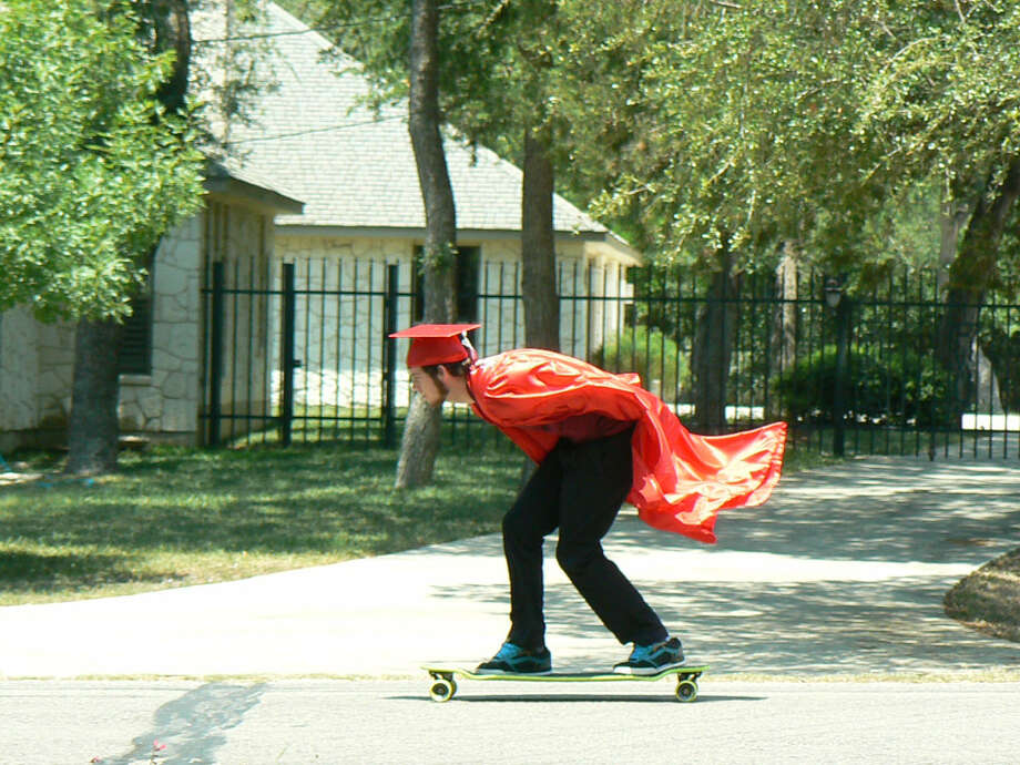 "Include an aspect of your graduate's favorite hobby in a photograph.  Graham Clumpner rides his longboard with his Canyon High School graduation robe on. ""Fits him to a T,"" says his mother Julie Kenfield in the email she submitted with the image. Photo: Courtesy Photos"