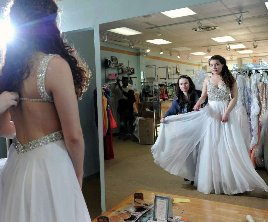 At right, Greenwich High School senior, Maya Edward, 17, tries on a prom dress with the help of Danna Lane, the owner of the A Step Ahead store in Stamford, Thursday, April 25, 2013. Photo: Bob Luckey / Greenwich Time