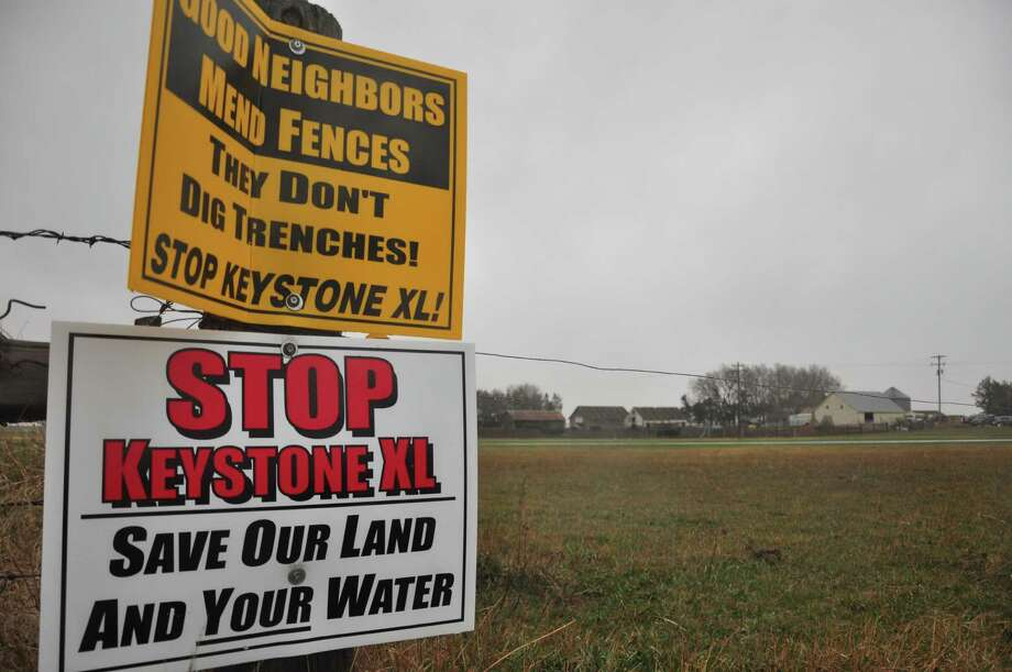 Signs attached to a fence on the property of Jim Tarnick, a farmer  opposed to the controversial Keystone XL pipeline, are pictured April 17, 2013 in Fullerton, Nebraska. The fence is on the exact route the pipeline would be on his land.  A lengthy battle over the controversial Keystone XL pipeline, which aims to funnel oil from Canada's tar sands to coastal Texas, heads to the most hotly contested area along the route on April 18, 2013.  Hundreds of people are expected at a public hearing in Nebraska's environmentally sensitive Sand Hills as the US State Department prepares its recommendation on whether to approve the $5.3 billion project.    AFP PHOTO / Guillaume MEYERGuillaume Meyer/AFP/Getty Images Photo: GUILLAUME MEYER / AFP
