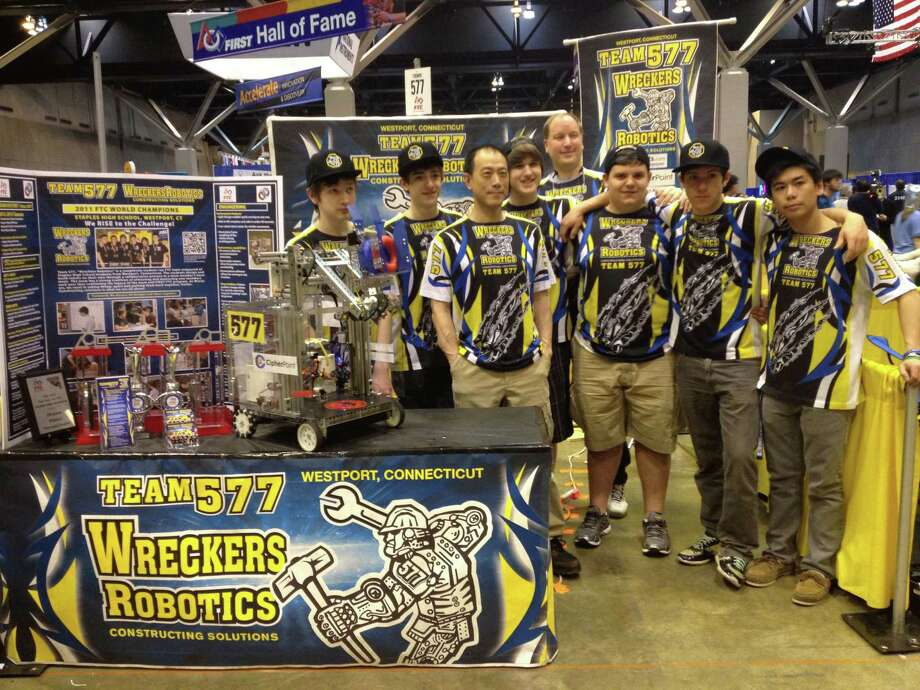 Wreckers Robotics Team 577 members stand with their robot, ìStacyî, in their FIRST world robotics championship team pit. From left, are:  Ian Blanchardon, Max Liben, mentor Michael Pan, co-captain Alec Solder, coach John Solder, Will Moeller, co-captain Troy Fantini, and Eric Pan. Photo: Contributed Photo / Westport News