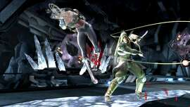 "Wonder Woman and Green Arrow fight in the Batcave in ""Injustice: Gods Among Us."""