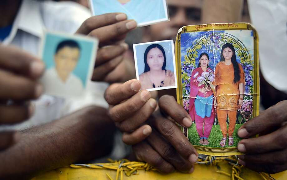 Family members hold portraits of their missing friends and family on Monday 29 April, 2013 in Savar, near Dhaka, Bangladesh. Rescue workers in Bangladesh gave up hopes of finding any more survivors in the remains of a building that collapsed five days ago, and began using heavy machinery on Monday to dislodge the rubble and look for bodies -- mostly of workers in garment factories there. At least 381 people were killed when the illegally constructed, 8-story Rana Plaza collapsed in a heap on Wednesday morning along with thousands of workers in the five garment factories in the building.(AP Photo/Ismail Ferdous) Photo: Ismail Ferdous, Associated Press