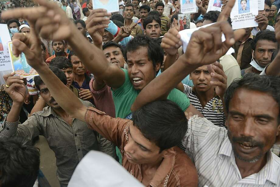 Protestors gather on the streets to demand for justice to those who were killed Monday 29 April, 2013 in Savar, near Dhaka, Bangladesh. Rescue workers in Bangladesh gave up hopes of finding any more survivors in the remains of a building that collapsed five days ago, and began using heavy machinery on Monday to dislodge the rubble and look for bodies -- mostly of workers in garment factories there. At least 381 people were killed when the illegally constructed, 8-story Rana Plaza collapsed in a heap on Wednesday morning along with thousands of workers in the five garment factories in the building.(AP Photo/Ismail Ferdous) Photo: Ismail Ferdous, Associated Press