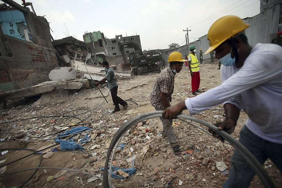 Workers clear rubble and debris at the garment factory building which collapsed in Savar, near Dhaka, Bangladesh, Monday April 29, 2013.  Rescue workers in Bangladesh gave up hopes of finding any more survivors in the remains of the building that collapsed five days ago, and began using heavy machinery on Monday to dislodge the rubble and look for bodies - mostly of workers in garment factories there. At least 381 people were killed when the illegally constructed, 8-story Rana Plaza collapsed in a heap on Wednesday morning along with thousands of workers in the five garment factories in the building.(AP Photo/Wong Maye-E) Photo: Wong Maye-E, Associated Press