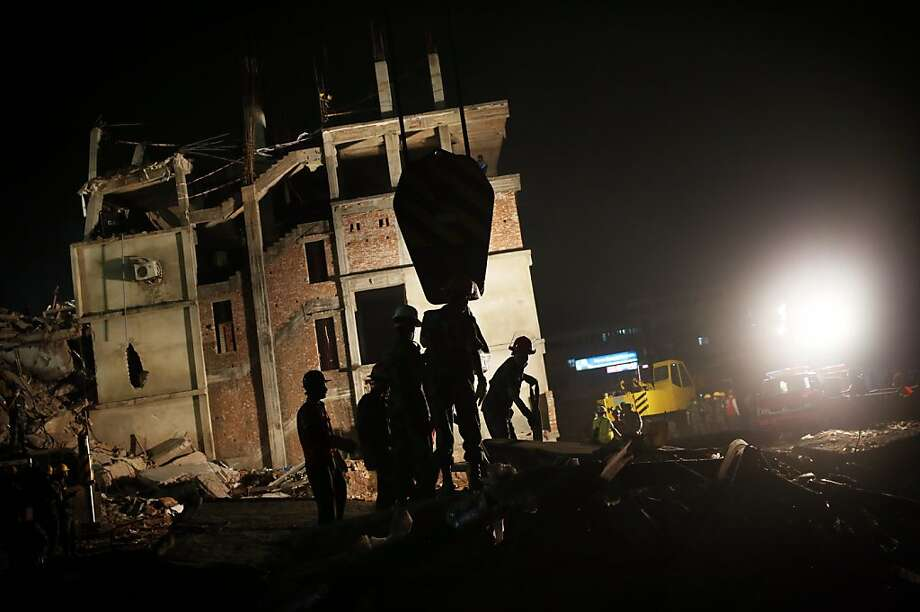 Firefighters and army personnel continue to work as dusk falls as they dislodge the debris and fallen ceiling of the garment factory building which collapsed in Savar, near Dhaka, Bangladesh, Monday, April 29, 2013. Rescue workers in Bangladesh gave up hopes of finding any more survivors in the remains of a building that collapsed five days ago, and began using heavy machinery on Monday to dislodge the rubble and look for bodies. At least 381 people were killed when the illegally constructed, 8-story Rana Plaza collapsed in a heap on Wednesday morning along with thousands of workers in the five garment factories in the building. (AP Photo/Wong Maye-E) Photo: Wong Maye-E, Associated Press
