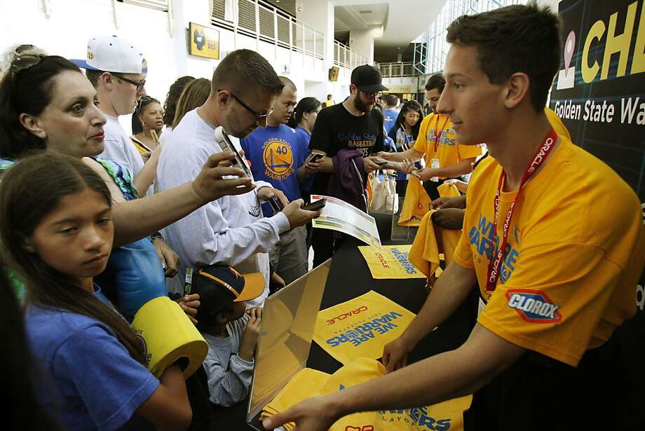Warriors fans show their smartphones after they checked in on Facebook to get rally towels before Sunday's playoff game against the Denver Nuggets. Fans were tipped off on social media as to various giveaways. Photo: Carlos Avila Gonzalez, The Chronicle
