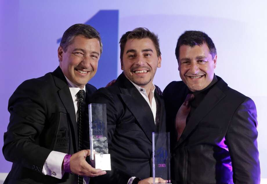 Head chef Joan Roca, left, accompanied by his brothers Jordi Roca, center, and Josep Roca, right,  pose for the photographers with their trophies after their restaurant El Celler de Can Roca in Girona, Spain, won the Best Restaurant.