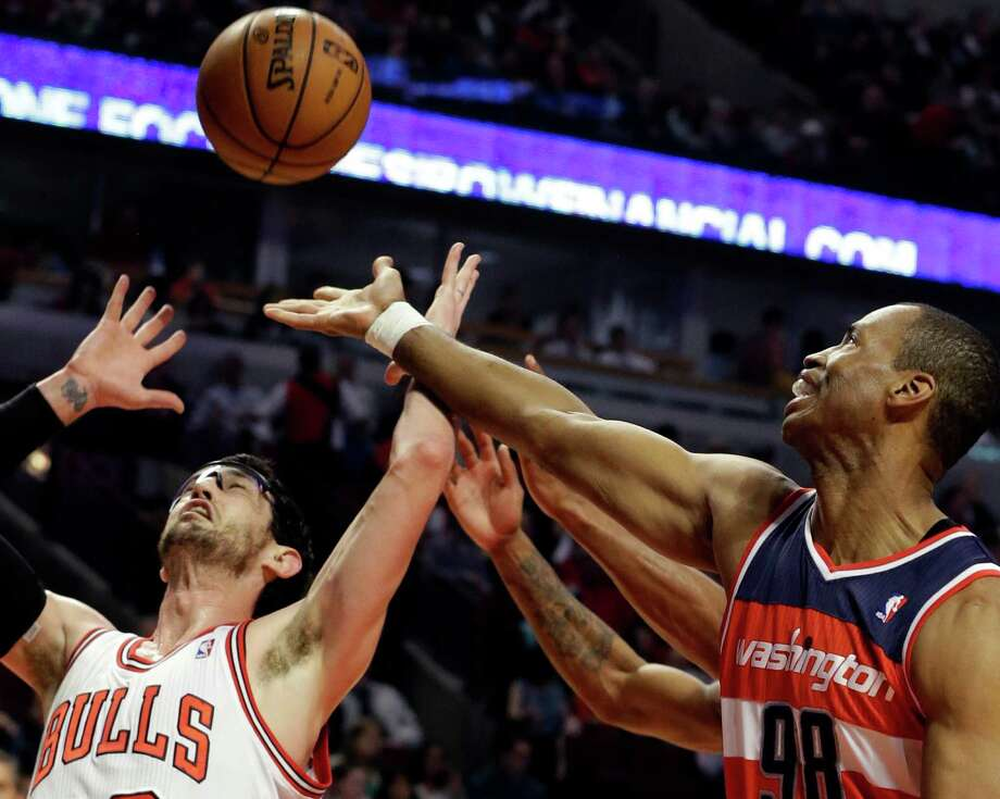 FILE - In a Wednesday, April 17, 2013 file photo, Washington Wizards center Jason Collins, right, battles for a rebound against Chicago Bulls guard Kirk Hinrich during the first half of an NBA basketball game in Chicago. NBA veteran center Collins has become the first male professional athlete in the major four American sports leagues to come out as gay. Collins wrote a first-person account posted Monday, April 29, 2013 on Sports Illustrated's website. (AP Photo/Nam Y. Huh, File) Photo: Nam Y. Huh