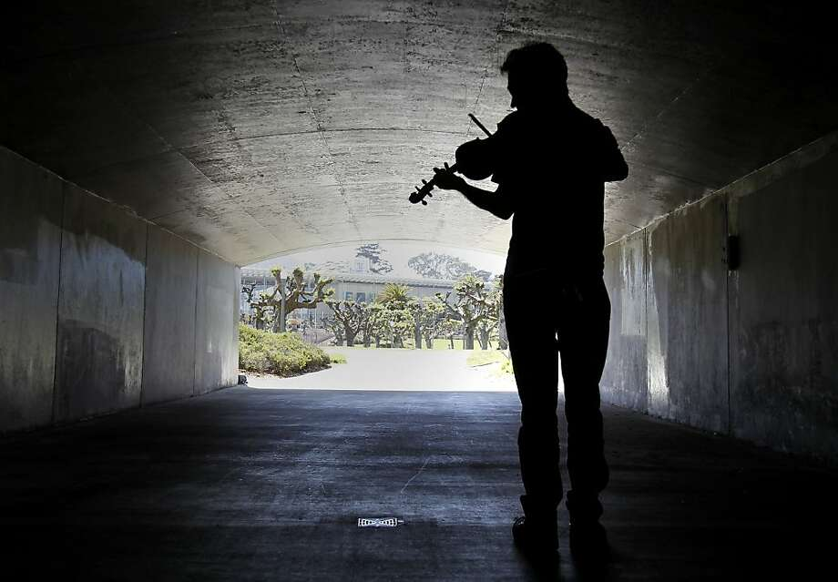 Jeremy Ennis experiments with the acoustics of a tunnel in Golden Gate Park while taking advantage of the shade as he plays his viola. Summerlike weather brought warmer temperatures even to the coastal areas. Photo: Brant Ward, The Chronicle