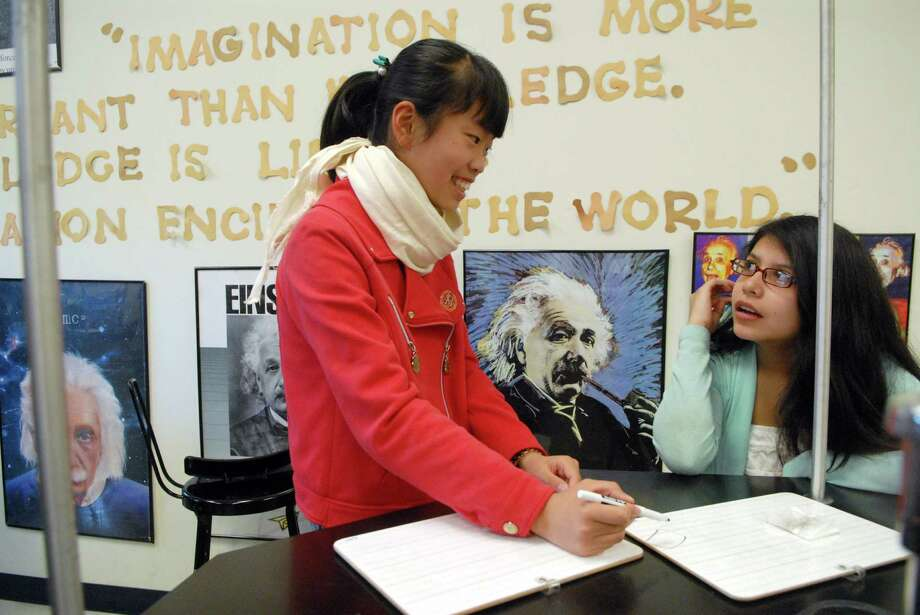 Man Gao works on a project with Shannon Guerra at Scofield Middle School in Stamford, Conn. on Monday April 29, 2013.. Gao is one of a group of  Chinese students visiting the school. Photo: Dru Nadler / Stamford Advocate Freelance