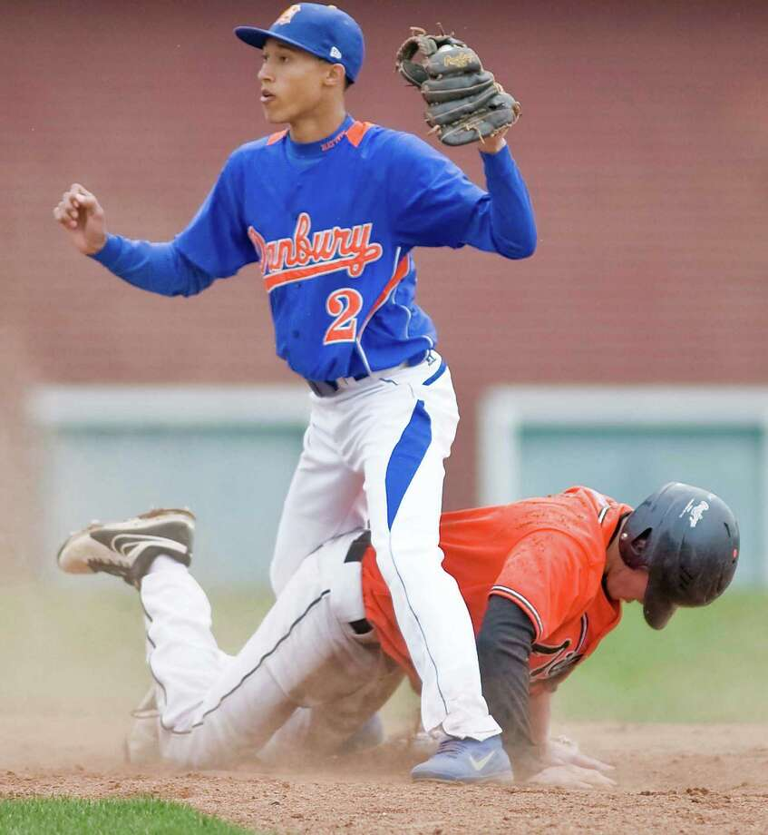 Danbury High School's Marquise Marrero gets tangled with Ridgefield High School's Robbie DePalma on a play at second base during a game at Danbury. Monday, April  29, 2013 Photo: Scott Mullin / The News-Times Freelance