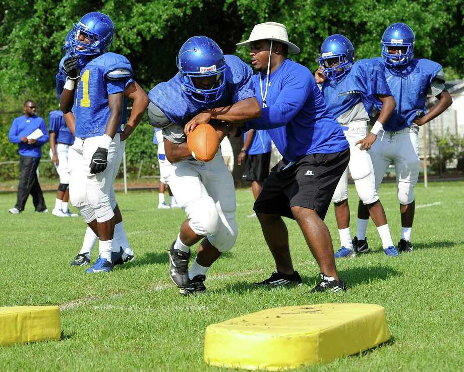 Coach Galen Douglas, right, gives ball handling instructions to some of his running backs. Monday afternoon, April 29, 2013, was the first day of spring football practice for the Ozen football team under the direction of new head coach Keeath Magee.    Dave Ryan/The Enterprise Photo: Dave Ryan
