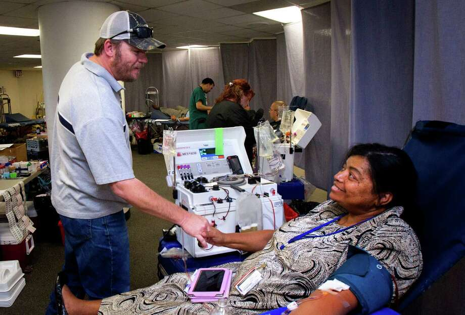 Harris County sheriff's Deputy Brian Bevil thanks Tanya Alexander for donating blood in his honor as he battles colon cancer. Photo: Cody Duty, Staff / Houston Chronicle