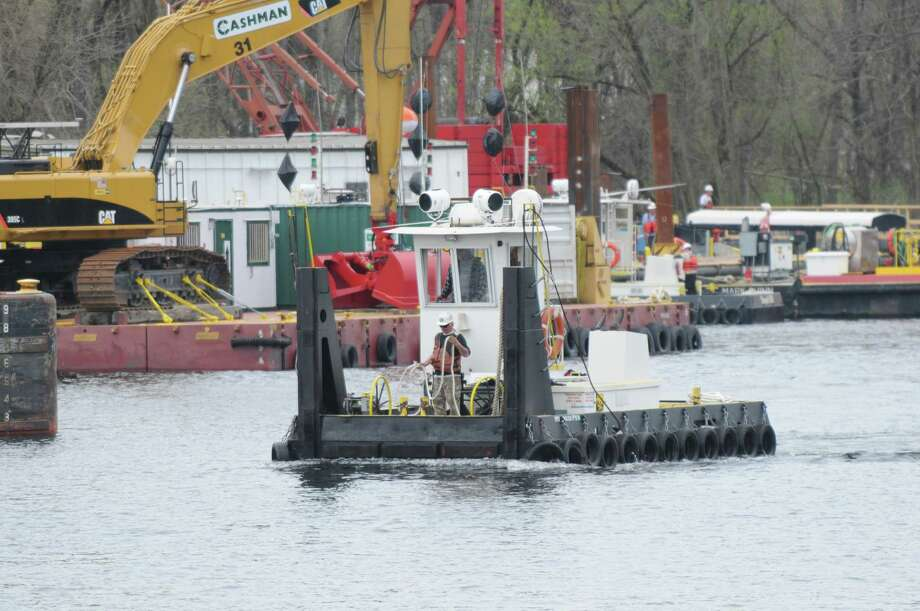 A small tug is maneuvered by dredging crews Monday, April 29, 2013, on the Hudson River just south of Fort Edward, N,Y. Monday marked the start of the fourth season of dredging to remove sediment contaminated with polychlorinated biphenyls (PCBs) in the Upper Hudson River. (Will Waldron/Times Union) Photo: Will Waldron