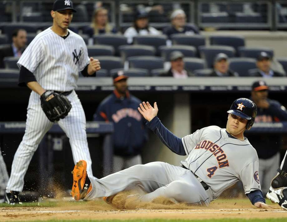 Brandon Laird of the Astros slides on a run batted in by Carlos Pena during the first inning. Photo: Bill Kostroun, Associated Press