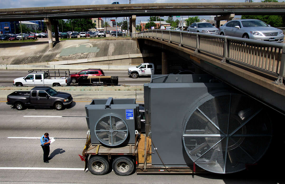 Police investigate an 18-wheeler after it got stuck going under the W Dallas St. overpass in the Northbound lane of I-45, Monday, April 29, 2013, in Houston.