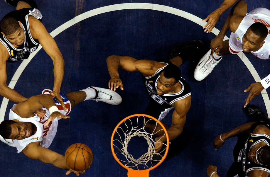 Jason Collins, then with the New Jersey Nets, pulls in a rebound in front of Spurs forward Tim Duncan (back left) and center David Robinson during the 2003 Finals. Photo: Kin Man Hui / San Antonio Express-News