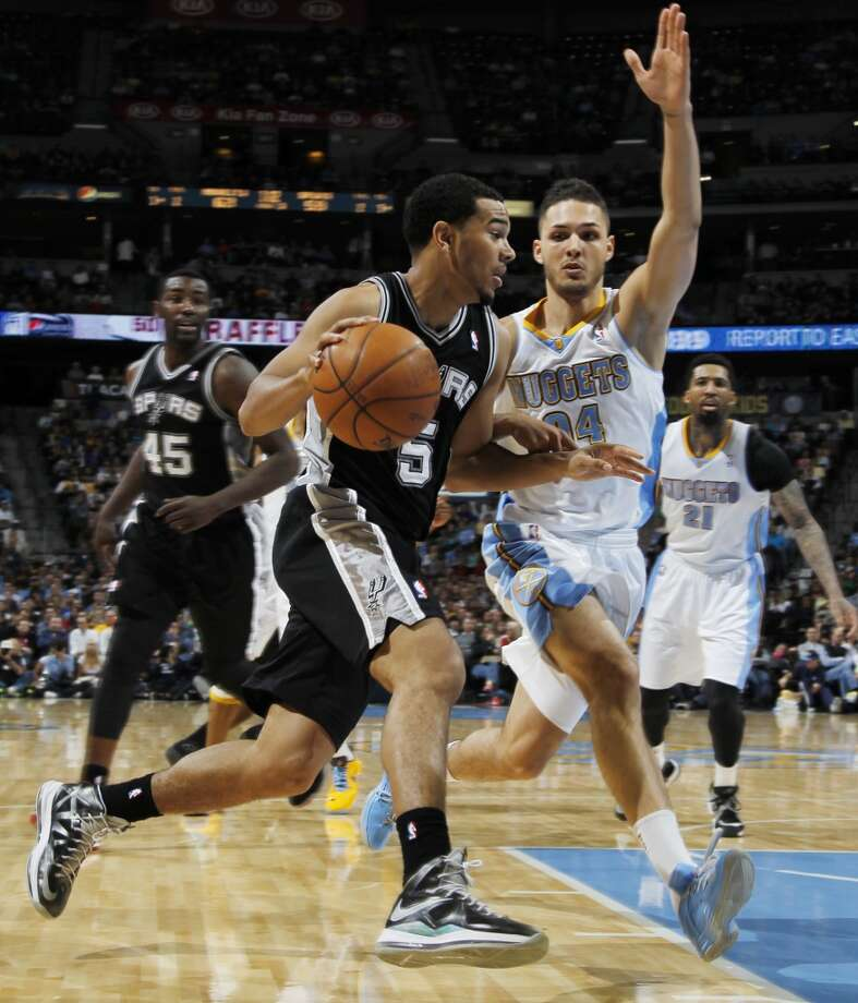 San Antonio Spurs guard Cory Joseph, left, drives for the basket as Denver Nuggets guard Evan Fournier, of France, covers in the third quarter of the Nuggets' 96-86 victory in an NBA basketball game in Denver on Wednesday, April 10, 2013. (AP Photo/David Zalubowski)