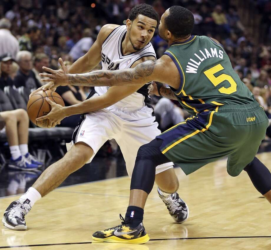 San Antonio Spurs' Cory Joseph looks for room around Utah Jazz's Mo Williams during first half action Friday March 22, 2013 at the AT&T Center.
