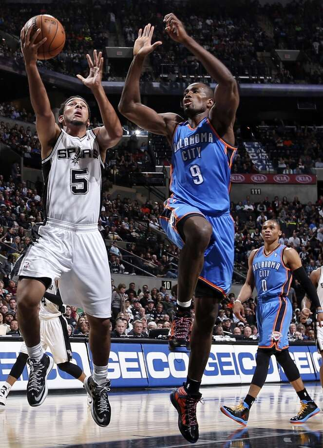 San Antonio Spurs' Cory Joseph shoots around Oklahoma City Thunder's Serge Ibaka during first half action Monday March 11, 2013 at the AT&T Center.