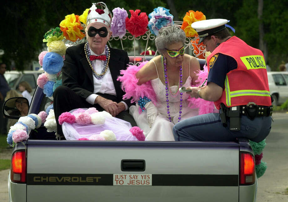 In this well-known 2001 photo, the people designated the King and Queen of the San Jose Senior Center receive a ticket from a policeman after they tossed candy to children along the parade route during the 60 Plus Mardi Gras Parade at Comanche Park that spring. Photo: Bob Owen