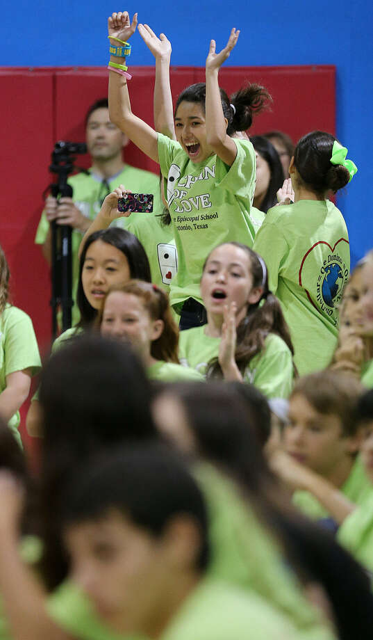 Seventh-grader Vicki Lozano reacts as students at St. George Episcopal School topple 15,000 dominoes during their Chain of Love event Monday. Photo: Jerry Lara / San Antonio Express-News