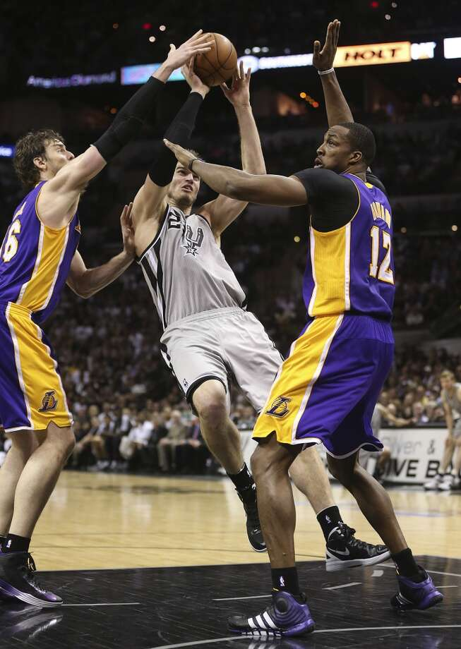 The Spurs' Tiago Splitter drives through the Lakers' Pau Gasol (left) and Dwight Howard during Game 1.  The Spurs won 91-79.
