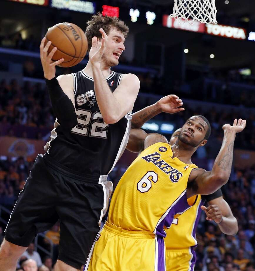 The Spurs' Tiago Splitter looks to pass around the  Lakers' Earl Clark during Game 3. Splitter suffered an ankle sprain at the end of the third quarter and missed the rest of Game 3 and all of Game 4.