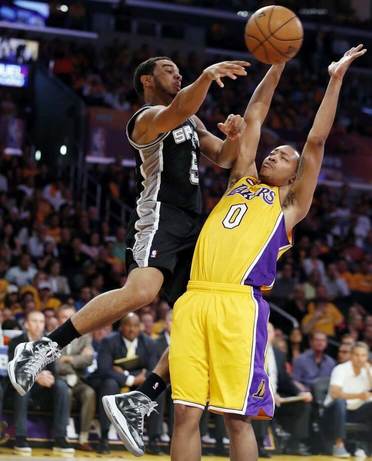 The Spurs' Cory Joseph passes around the Lakers' Andrew Goudelock. The Spurs pulled away by scoring 35 points in the fourth quarter during the Spurs' 120-89 Game 3 victory in Los Angeles.
