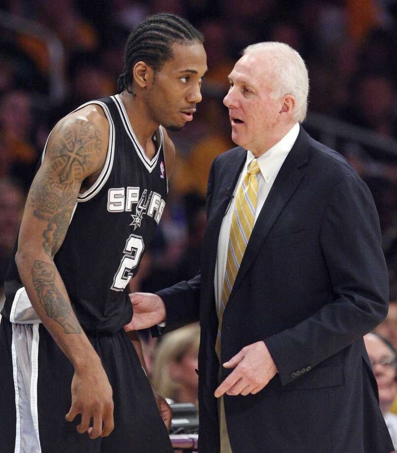 The Spurs' Kawhi Leonard talks with coach Gregg Popovich during the Spurs' 120-89 Game 3 victory in Los Angeles.
