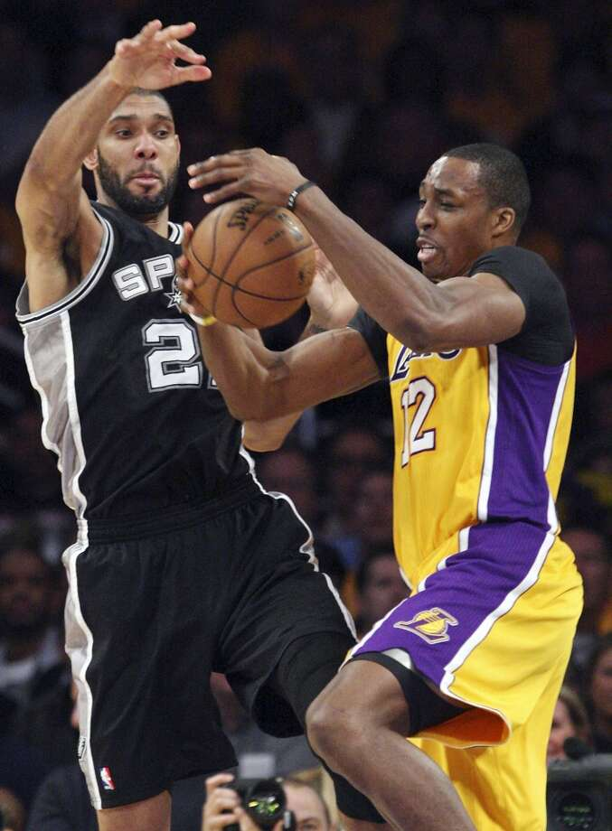 The Spurs' Tim Duncan and Lakers' Dwight Howard grab for a loose ball during the Spurs' 120-89 Game 3 victory in Los Angeles.