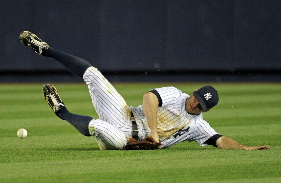 New York's Brett Gardner is unable to catch a single by Houston's Jose Altuve. Photo: Bill Kostroun / Associated Press