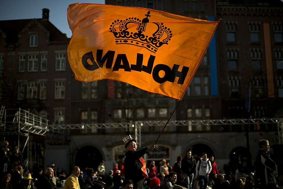 A man waves a flag with the color of the House of Orange of the Dutch Royal Family in Dam square in downtown Amsterdam, Netherlands Monday, April 29, 2013. Queen Beatrix has announced she will relinquish the crown on April 30, 2013, after 33 years of reign, leaving the monarchy to her son Crown Prince Willem Alexander. (AP Photo/Emilio Morenatti) Photo: Emilio Morenatti, Associated Press
