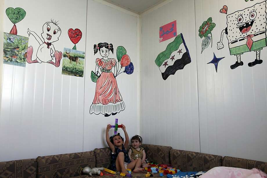 Syrian refugees, Noray Karaman, right, who was born in her family home by Caesarean section, and her sister, Sedrat, 3, play with their toys at their family's trailer, at the Zaatari refugee camp, near the Syrian border, in Mafraq, Jordan, Monday, April 29, 2013. Jordan's economy is ailing and some lawmakers have expressed concerns over the rising numbers of Syrian refugees in the resource-poor kingdom. (AP Photo/Mohammad Hannon) Photo: Mohammad Hannon, Associated Press