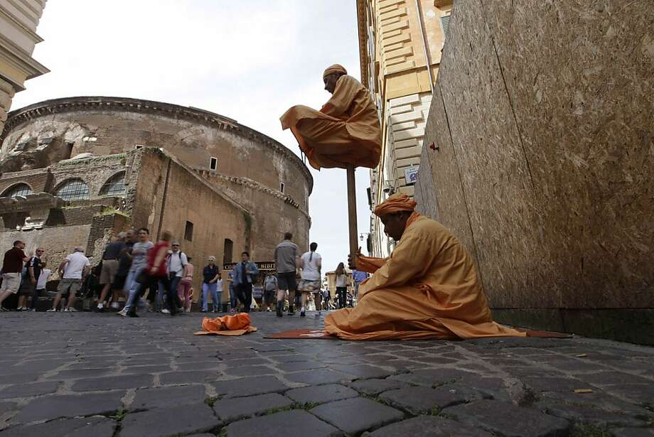 Seeing is not believing:Either this street performer is exceptionally strong or something fishy is going on under those robes. (Pantheon in Rome.) Photo: Alessandra Tarantino, Associated Press