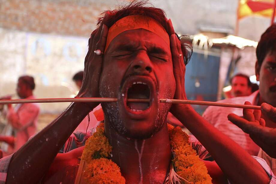 An Indian devotee reacts in pain as a steel trident pierced through his cheeks as part of a ritual, is removed after a religious procession to the temple of Hindu goddess Sheetala Mata or Muthumariamman in Ahmadabad, India, Monday, April 29, 2013. The devotees perform the ritual after their prayers to the goddess have been answered or their wishes fulfilled. In Hinduism, goddess Sheetala Mata, is considered an aspect of Shakti or power. (AP Photo/Ajit Solanki) Photo: Ajit Solanki, Associated Press