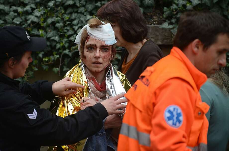 TOPSHOTS A police woman and paramedic wrap a thermo foil around a woman injured by a powerful gas blast on April  29, 2013 in Prague's historic center. The blast injured up to 20 people, four seriously, rescuers said, adding that it was possible some people were buried in the rubble. AFP PHOTO / MICHAL CIZEKMICHAL CIZEK/AFP/Getty Images Photo: Michal Cizek, AFP/Getty Images