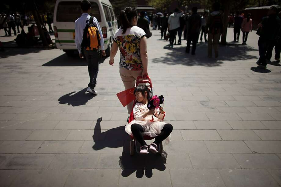 A girl holds a Qing Dynasty royal style headset while her mom drags her with a shopping stroller after the family toured the Forbidden City in Beijing, China, Monday, April 29, 2013. Monday is the first day of a 3-day public holiday celebrating the upcoming International Workers' Day on May 1. (AP Photo/Alexander F. Yuan) Photo: Alexander F. Yuan, Associated Press