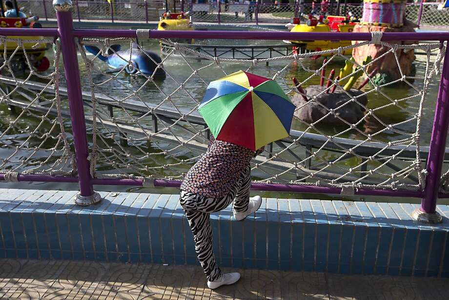 A child wearing an umbrella hat visits the water themed attraction at a park in Beijing Monday, April 29, 2013. Monday is the first day of a three-day public holiday celebrating the upcoming international workers' day on May 1. (AP Photo/Ng Han Guan) Photo: Ng Han Guan, Associated Press