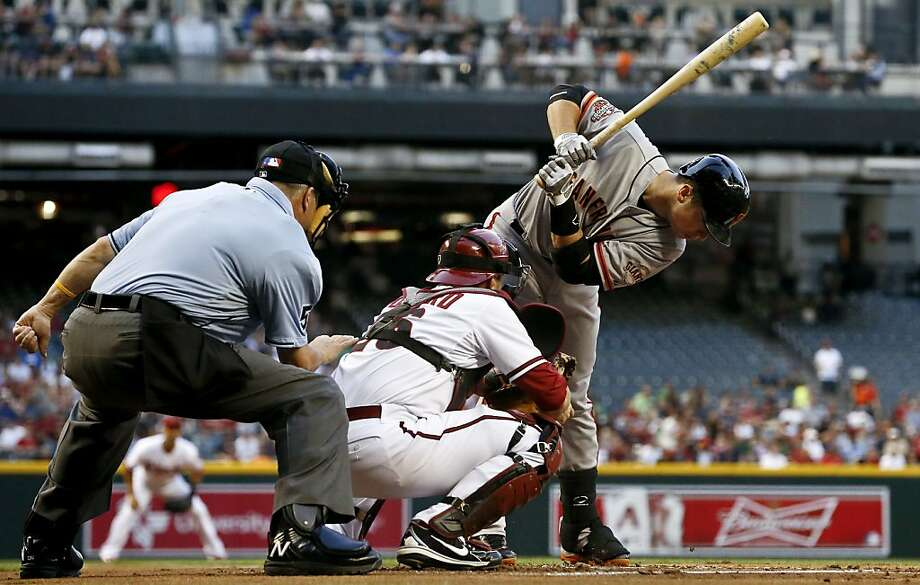 San Francisco Giants' Buster Posey bends out of the way of a pitch as Arizona Diamondbacks catcher Miguel Montero gets the inside pitch and umpire Dale Scott watches during the first inning of a baseball game on Monday, April 29, 2013, in Phoenix. (AP Photo/Ross D. Franklin) Photo: Ross D. Franklin, Associated Press
