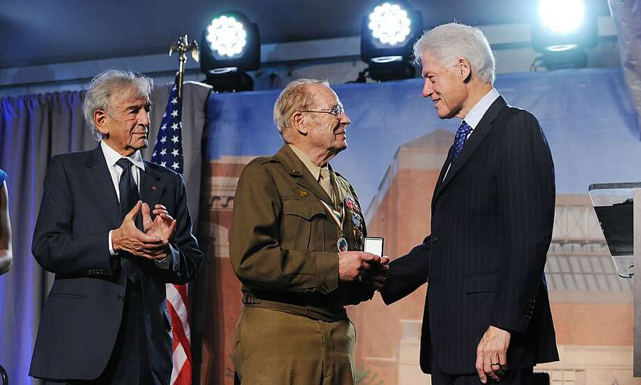 World War II veteran Scottie Ooton (center) who helped to liberate a concentration camp and Holocaust survivor and author Elie Wiesel (left) are presented with pins by former U.S. President Bill Clinton during the 20th anniversary National Tribute at the United States Holocaust Memorial Museum April 29, 2013 in Washington, DC. The Museum was hosting a two-day tribute event to honor Holocaust survivors and World War II veterans to mark its 20th anniversary. (Olivier Douliery/Abaca Press/MCT) Photo: Olivier Douliery, McClatchy-Tribune News Service